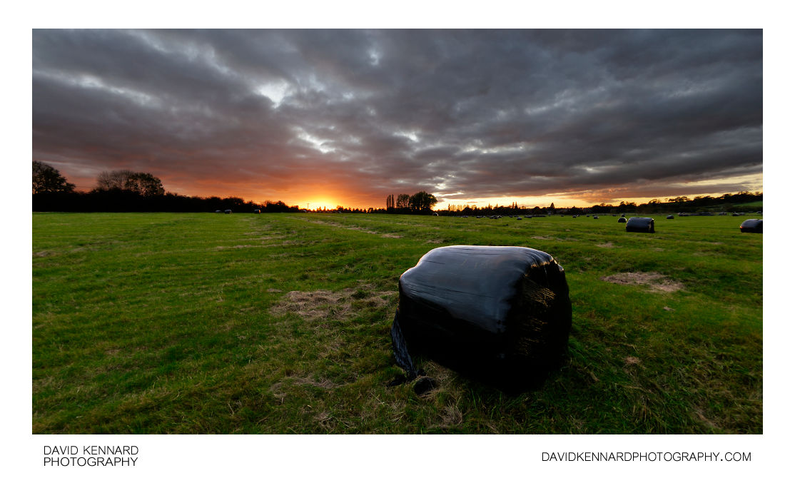 Sunset and black plastic wrapped haybale
