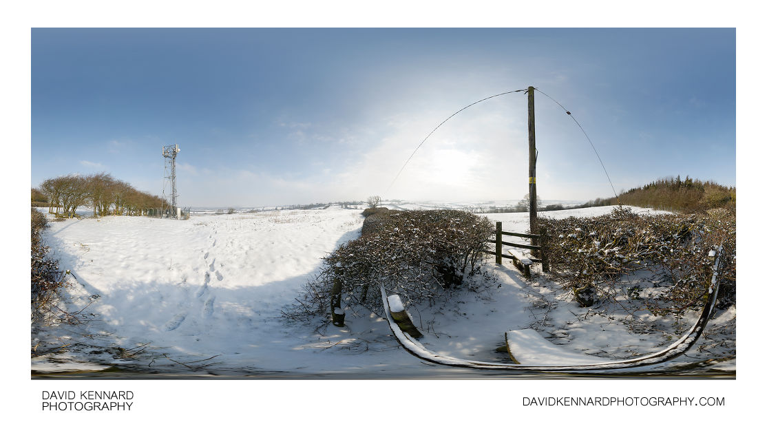 Stile near radio tower in the snow, East Farndon