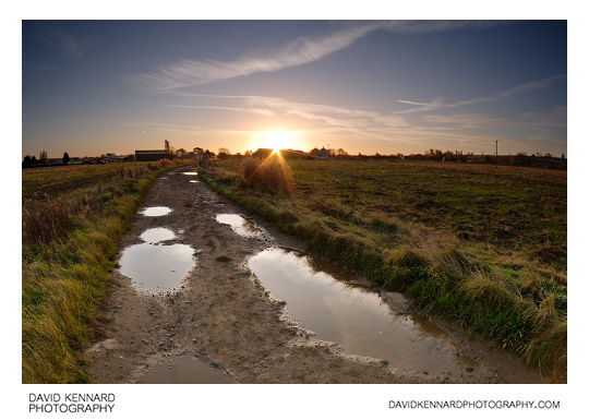 Sunrise over a puddle filled track across Farndon Fields