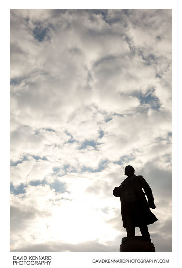 A monument to Vladimir Ilyich Lenin silhouetted against a cloudy sky in Dnipropetrovsk, Ukraine. The statue stands on Lenina Square, just off Karla Marksa Avenue, in the Babushkinskiy Raion of central Dnipropetrovsk.