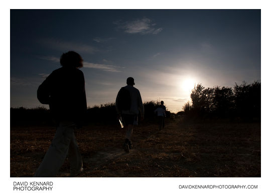 Silhouette of family walking through field