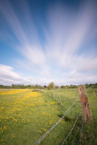 Long exposure photo of a fence surrounding a buttercup meadow, taken with Zomei 6 stop and XCSource 10 stop ND filters