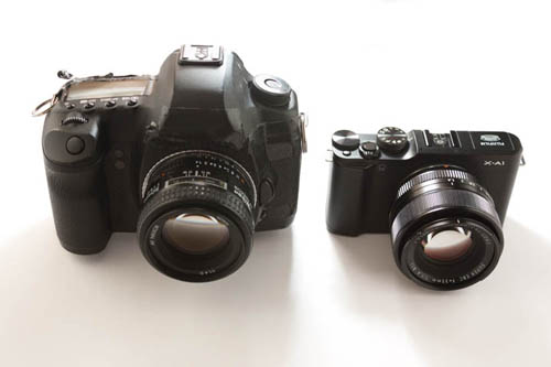 Canon 5D Mk II DSLR camera with Nikon 50mm f/1.4 lens compared in size to Fuji X-A1 Mirrorless Camera with Fuji 35mm f/1.4 lens