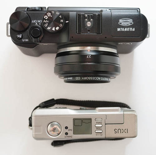 Fuji X-A1 Mirrorless Camera with Fuji 27mm f/2.8 lens compared in size to Canon Ixus Elph compact APS film camera (top down view)
