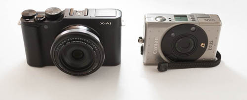Fuji X-A1 Mirrorless Camera with Fuji 27mm f/2.8 lens compared in size to Canon Ixus Elph compact APS film camera