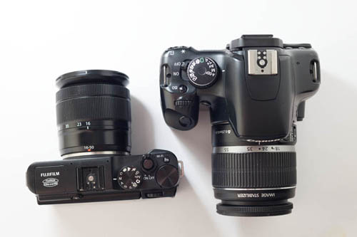 Fuji X-A1 Mirrorless Camera with Fuji 16-50mm f/3.5-5.6 zoom lens compared in size to Canon Rebel DSLR with 18-50mm f/3.5-5.6 zoom lens (top down view)