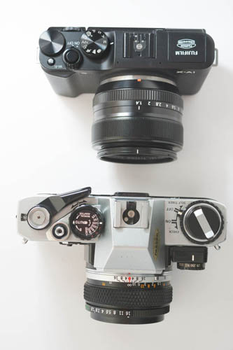 Fuji X-A1 Mirrorless Camera with Fuji 35mm f/1.4 lens compared in size to Olympus OM10 SLR camera with OM 50mm f/1.8 lens (top down view)