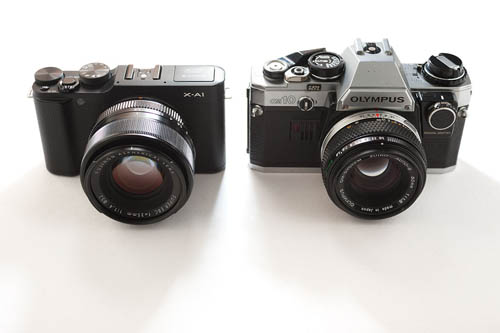 Fuji X-A1 Mirrorless Camera with Fuji 35mm f/1.4 lens compared in size to Olympus OM10 SLR camera with OM 50mm f/1.8 lens