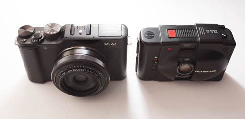 Fuji X-A1 Mirrorless Camera with Fuji 27mm f/2.8 lens compared in size to Olympus XA 2 compact 35mm film camera