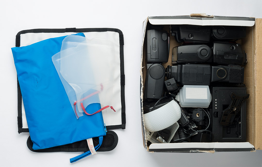 Main flash box with top layers of flash bouncer, milk bottle diffusers and pack of filter gels removed. In the box are speedlight flashes, various flash accessories, and a small LED light panel.