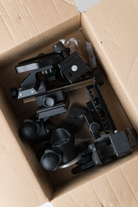 Tripod heads in a cardboard box, not arranged in any fashion other than to fit them in the box
