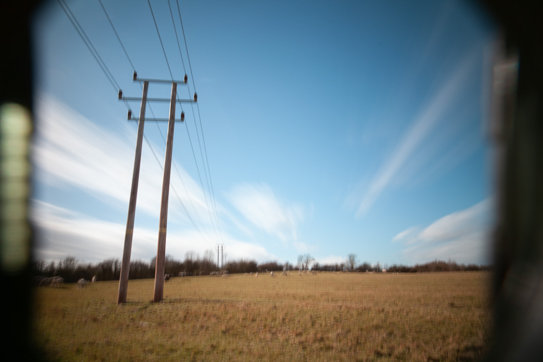 Photo of power lines crossing a field taken on a standard Canon 5D Mark II camera with SLR Magic Image Enhancer Pro UVIR cut filter, XCSource 10 stop glass ND filter and Hitech 1, 2, and 3 stop plastic ND filters