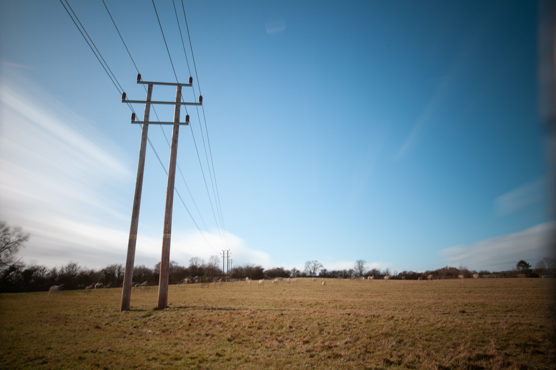 Photo of power lines crossing a field taken on a standard Canon 5D Mark II camera with a wide-angle lens with XCSource 10 stop glass ND filter and Hitech 1, 2, and 3 stop plastic ND filters