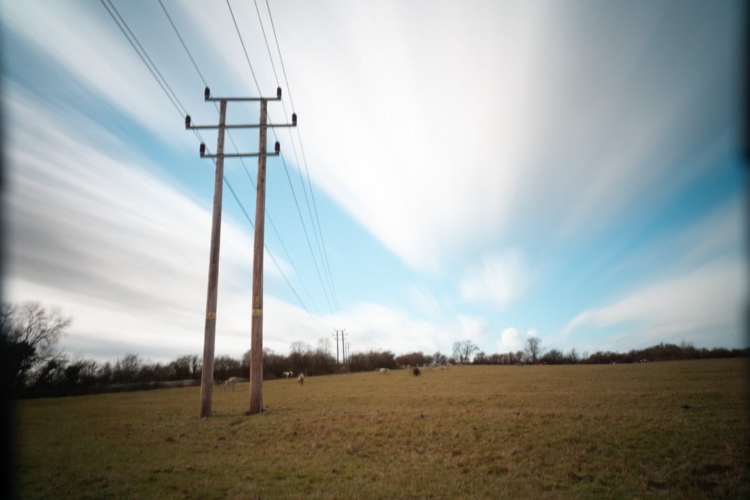 Photo of power lines crossing a field taken on a standard Fuji X-A1 camera with SLR Magic Image Enhancer Pro UVIR cut filter, XCSource 10 stop glass ND filter and Hitech 1, 2, and 3 stop plastic ND filters