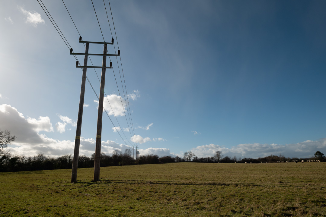 Photo of power lines crossing a field taken on a standard Fuji X-A1 camera with a wide-angle lens with SLR Magic Image Enhancer Pro filter