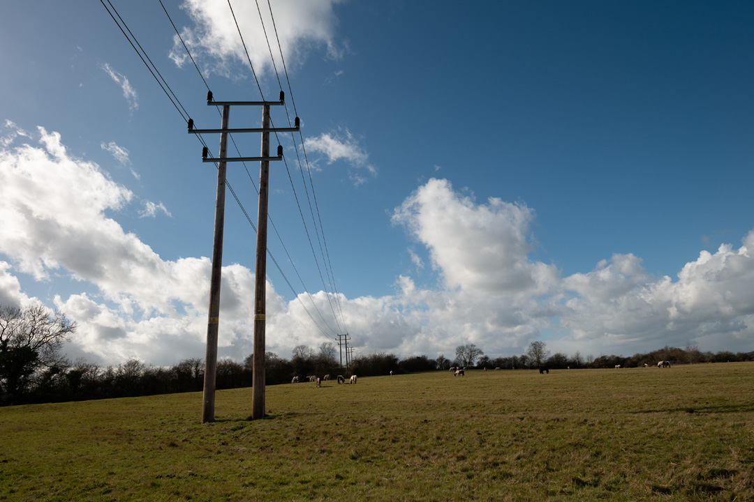 Photo of power lines crossing a field taken on a standard Fuji X-A1 camera with a wide-angle lens with no filter