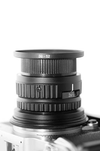 Fujifilm X-M1 camera with DIY M42 adapter and reversed 50mm f/2.8 N EL-Nikkor lens attached
