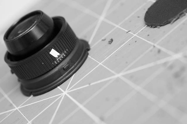 Small pieces of tape used to mark the tab positions by placing the adapter over a Lensbaby optic. The ridges on the adapter where the tab is to be positioned have been cut away.