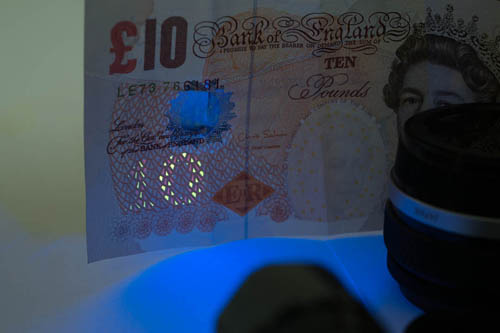 Photo of a British £10 note showing the UV security feature lit by the Ultrafire G60 3w UV torch with the front glass replaced with the 330WB70 Excite Fluorescence filter, with the black side of the filter facing out.