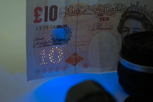 Photo of a British £10 note showing the UV security feature lit by the Ultrafire G60 3w UV torch with the front glass replaced with the 330WB70 Excite Fluorescence filter, with the reflective side of the filter facing out.