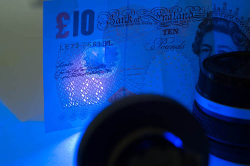 Photo of a British £10 note showing the UV security feature lit by the Ultrafire G60 3w UV torch shining through a Baader U filter with the pink side facing out.