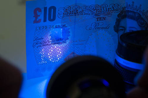 Photo of a British £10 note showing the UV security feature lit by the Ultrafire G60 3w UV torch shining through a Baader U filter with the gold side facing out.