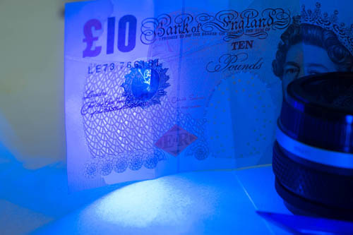 Photo of a British £10 note showing the UV security feature lit by cheap Aluminium UV Ultra Violet Blacklight 9 LED AAA Flashlight Torch Light Lamp