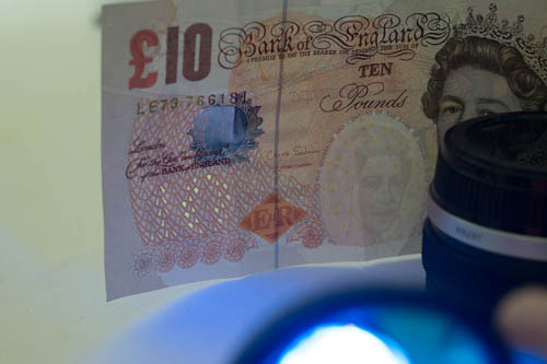 Photo of a British £10 note showing the UV security feature lit by cheap Aluminium UV Ultra Violet Blacklight 9 LED AAA Flashlight Torch Light Lamp shining through Baader U filter.